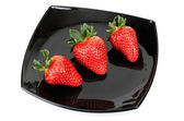 Three fresh strawberries on black saucer isolated on white — Stock Photo