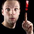 Royalty-Free Stock Photo: Surprised man shows red exclamation mark  isolated on black background