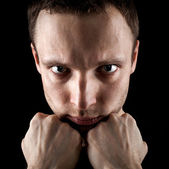 Serious young Caucasian man's portrait. Close-up face with fists on black background — Stock Photo