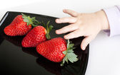 Little baby's hand reaches for strawberries — Stock Photo