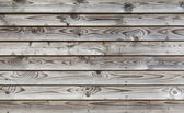 Uncolored weathered gray wooden lining boards — Stock Photo