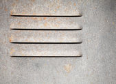 Fragment of an old gray metal wall with ventilation grille — Stock Photo