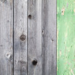 Background texture of old gray weathered wooden lining boards with one green painted plank — Stock Photo #22672197