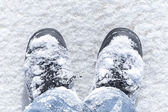 Winter walking, man's legs in boots with show on it — Stock Photo