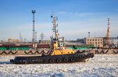 Piccolo rimorchiatore passa attraverso il canale ghiacciato nel porto di san pietroburgo porta di carico — Foto Stock
