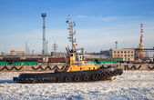 Small tug boat goes through icy channel in harbor of St.Petersburg cargo port — Stock Photo