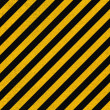 Seamless background pattern with yellow and black diagonal lines on concrete wall — Stock Photo #22865560