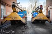 Dos camiones de servicio alimentación amarillo con flechas de señales azules — Foto de Stock