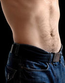 Man's belly with jeans. Closeup photo on black with shallow depth of field — Foto Stock