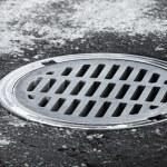 Sewer manhole on the urban asphalt road. Closeup photo — Stock Photo #23092158