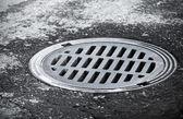 下水道マンホール都市アスファルト道路上。クローズ アップ写真 — ストック写真