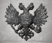 Double Eagle - Emblem of Russia. Ancient black bas-relief on gray vintage wall — Stock Photo