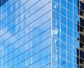 Coin de l'immeuble moderne aux reflets de ciel bleu lumineux dans windows — Photo