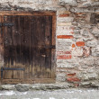 Stone wall of an ancient fortress with dark wooden door. Tallinn, Estonia — Stock Photo #23386566