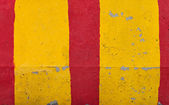 Red and yellow striped road barrier concrete wall texture — Stock Photo