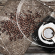 Cup of espresso coffee with beans and canvas on weathered wooden table. Coffee break metaphor illustration - Stock Photo
