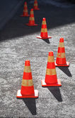 Red and yellow striped warning cones in line on asphalt road — Stock Photo