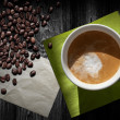Cup of cappuccino coffee, old paper sheet, green napkin and beans on black wooden table, top view — Stockfoto