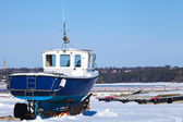 Small blue boat on the snowy coast of Baltic Sea in winter — Stockfoto