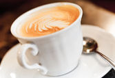 Cappuccino coffee with spice and artistic foam in a white cup — Stock Photo