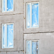 Unfinished building concrete wall with windows. Under construction - Stock Photo
