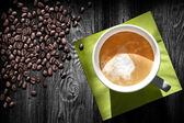 Cup of cappuccino coffee, green napkin and beans on black wooden table, top view — Stok fotoğraf