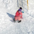 Little girl in pink drives off with a squeal from the icy hill for fun — Stock Video