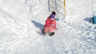 ピンクの女の子の楽しみのための氷の丘から甲高い音とともにドライブします。 — ストックビデオ