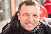 Close up city outdoor portrait of young smiling man in cold season — Stock Photo
