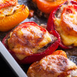 Bell peppers stuffed with chopped meat, cheese and tomato on black baking pan — Stock Photo