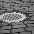 Stock Photo: Old sewer manhole on dark cobblestone pavement