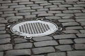 Old sewer manhole on dark cobblestone pavement — Stock Photo