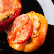 Stock Photo: Stuffed bell peppers with chopped meat, cheese and tomato on black plate