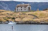 Vieja abandonada casa de madera gris y pequeñas lanchas modernas en la costa de noruega — Foto de Stock