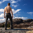 Topless strong man stands on the mountain and looks down — Stock Photo