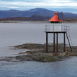 Norwegian lighthouse tower on rocks with solar battery and red top - Stok fotoğraf
