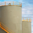 Gray cylindrical fuel tanks with yellow railings above blue cloudy sky — Stock Photo #25478227
