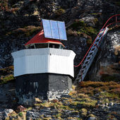 Traditional Norwegian lighthouse tower on small rocky island with solar battery and red top — Stock Photo