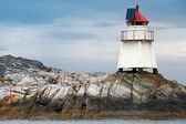 Traditional Norwegian lighthouse. White tower on rocky island with solar battery and red top — Stok fotoğraf