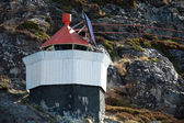 Norwegian lighthouse tower on rocky island with red top — Stock Photo