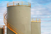 Gray cylindrical fuel tanks with yellow railings above blue cloudy sky — Stock Photo