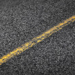 Asphalt road with yellow solid line. Transportation background texture — Stockfoto #25536229
