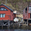 Traditional Norwegian red wooden boat barns on the sea coast. Old and new one next to — Stock Photo
