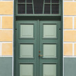 Green door with decoration elements in old building facade. Tallinn, Estonia — Stock Photo