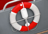 Red and white lifebuoy with rope in small boat — Stock Photo