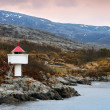 Norwegian lighthouse. White tower red top stands on coastal rocks - Stock Photo