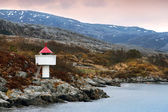 Norwegian lighthouse. White tower red top stands on coastal rocks — Stok fotoğraf