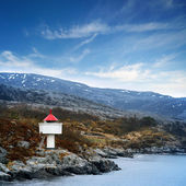 Norwegian lighthouse. White tower red top stands on coastal rocks under blue sky — Stok fotoğraf