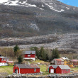 Traditional small Norwegian village with red wooden houses on rocky coast with mountains on the horizon — Stock fotografie