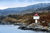 Norwegian lighthouse. White tower with red top stands on coastal rocks — Foto Stock